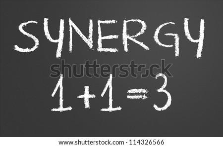 Synergy 1 +1 = 3 written on a chalkboard - stock photo