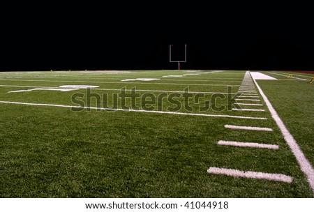 Synthetic turf football field at night - stock photo
