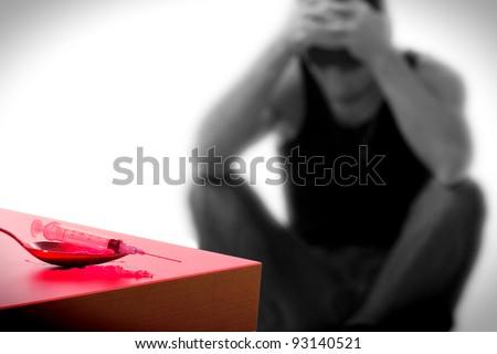 syringe and drug addict, sitting in the background - stock photo