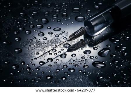 Syringe and needle , water drops background,dramatic lighting - stock photo