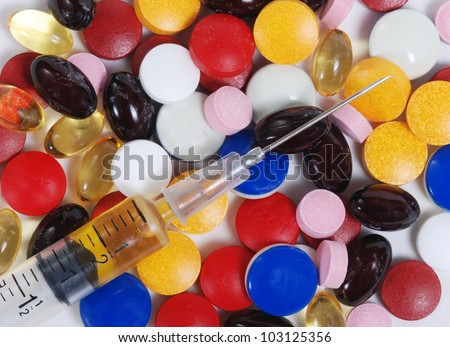 Syringe and variety of pills.  Isolated on white. - stock photo