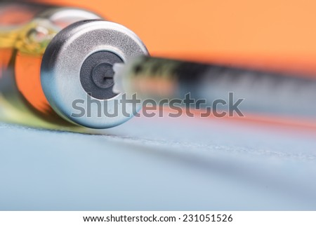 Syringe extracting serum from an ampoule against blue background - stock photo