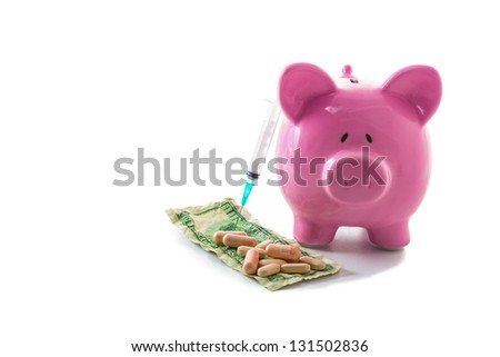 Syringe leaning against piggy bank with dollars and pills on white background - stock photo