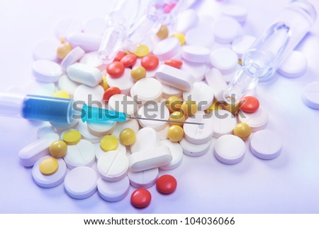 syringe on the background of tablets and pills.