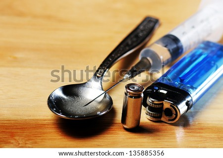 syringe, spoon ,bullet and lighter on the floor - stock photo