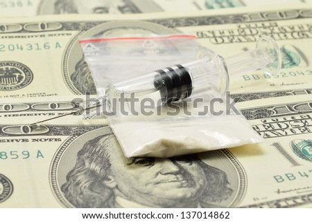 syringe with a drug is on the money with white powder - stock photo