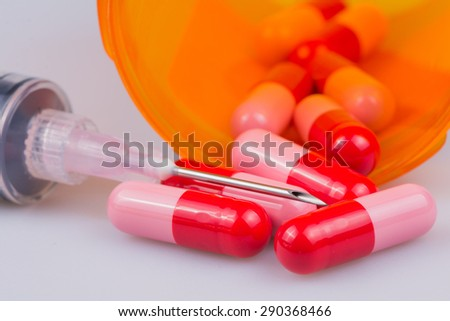 Syringe with a needle laying over prescription pill capsules.  - stock photo