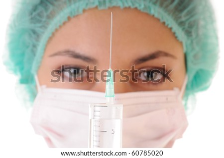 Syringe with solution for injection and woman in mask and cap on background. Focus on the syringe. - stock photo