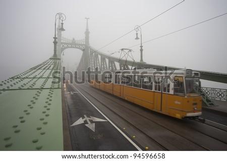 Szabadsag hid, liberty bridge, monumental austro hungarian green bridge in fog with orange tram passing - stock photo