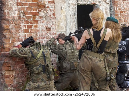SZCZECIN, POLAND - MAY 31, 2014: Attractive womens in military uniform, holding gun and aim to shoot, during Historical reenactment. - stock photo