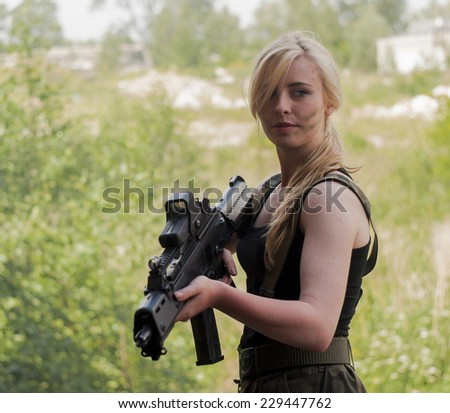 SZCZECIN, POLAND - MAY 31, 2014: Beautiful sexy blond woman holding army weapon, during historical reconstruction - stock photo