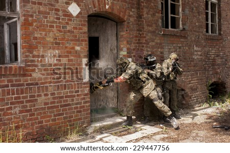 SZCZECIN, POLAND - MAY 31, 2014: Three soldiers in full uniform stormed the building, during historical reconstruction - stock photo