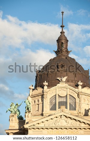 Szechenyi thermal bath, Budapest, Hungary at the rising sun in clear sky and fluffy clouds - stock photo