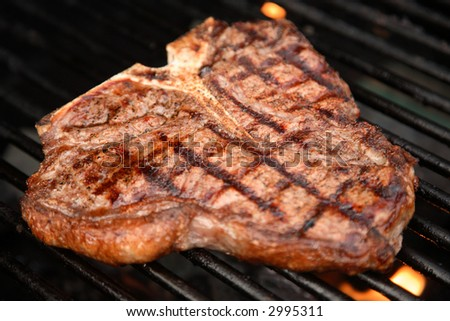 t-bone steak cooking on an open flame grill - stock photo