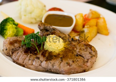 T-Bone steak with mashed potato and herb butter