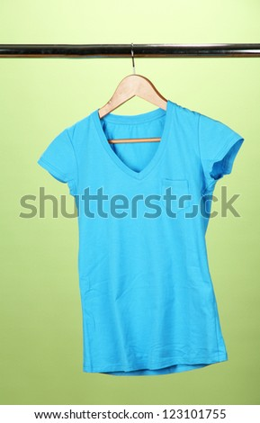 T-shirt on wooden hanger, on green background
