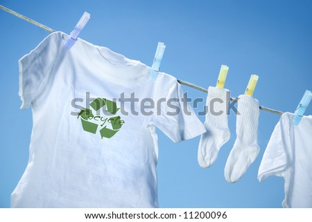 T-shirt with recycle logo drying on clothesline on a summer day - stock photo