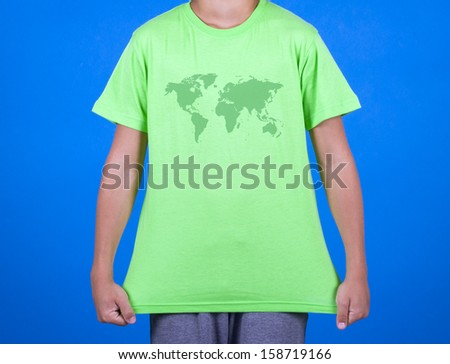 T-shirt with the image of a world map on a pretty boy. - stock photo
