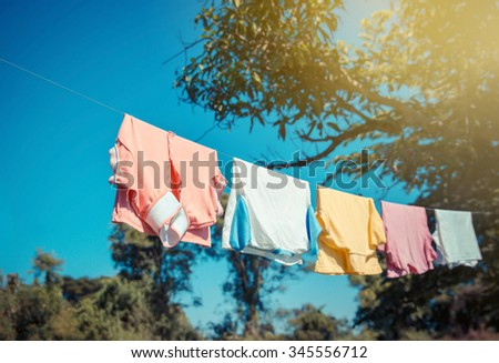 T-shirts hanging on a clothesline with blue sky - stock photo