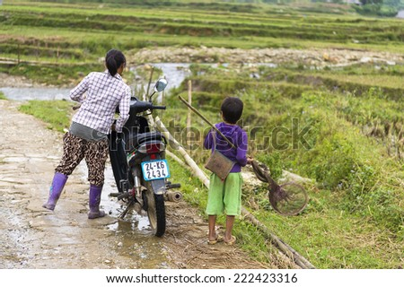 TA PHIN, LAO CAI, VIETNAM - SEP 21, 2014: Unidentified Red Dao woman with her child on her motorbin the Ta Phin village. Red Dao is one of the minority ethnic groups in Vietnam