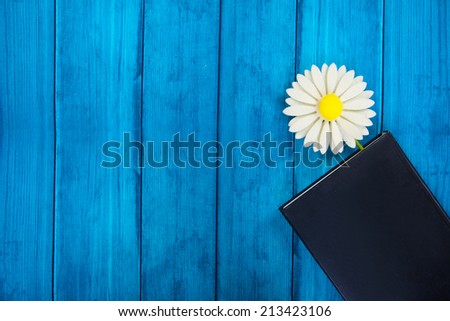 tab in the diary in the form of a flower on a blue wooden background - stock photo