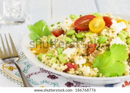 Tabbouleh made with bulgar, edamame, red and yellow cherry tomatoes, green onions, cilantro, crumbled feta cheese and a lemon pesto dressing - stock photo