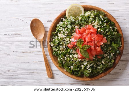 Tabbouleh salad in a wooden bowl on the table. horizontal view from above  - stock photo