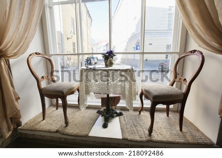 Table and chairs by window in empty cafe - stock photo