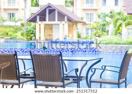 table and chairs in outdoor cafe, small restaurant at hotel poolside, summer vacations, meal time - stock photo