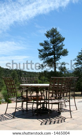 Table and chairs on a patio in the mountains - stock photo