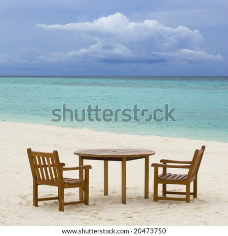 Table and chairs on tropical beach - stock photo
