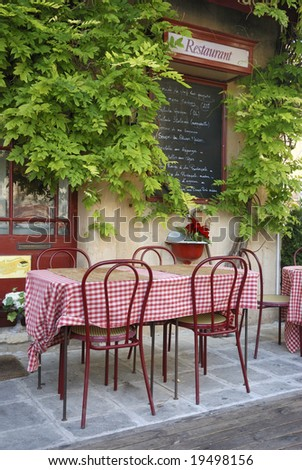 Table and chairs outside a French restaurant with menu sign against the wall - stock photo
