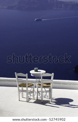 Table and chairs overlooking on a clear day at Santorini, Greece with ship in the background. - stock photo