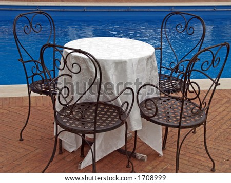 Table and four chairs near the pool - stock photo
