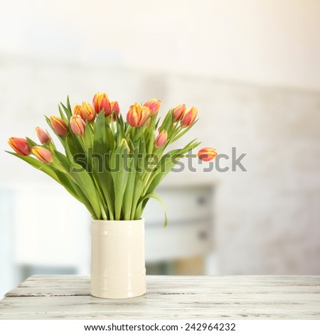 table and jug of flowers  - stock photo