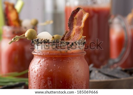 Table arrangement with pepper smoked bacon bloody mary or caesar in mason jars - stock photo