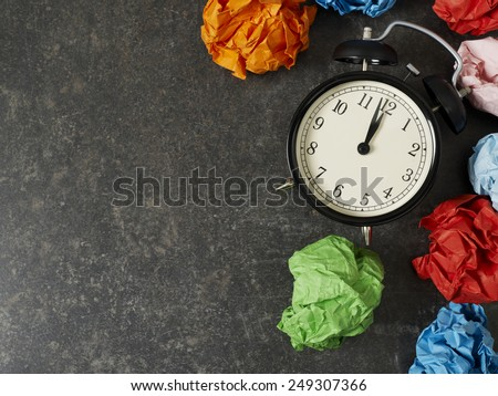 Table clock and paper balls with copyspace - stock photo