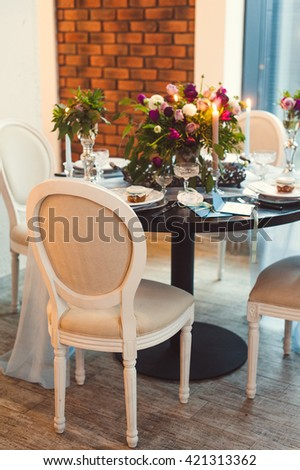 table decoration. beautiful bouquet of flowers, candles, glasses and plates