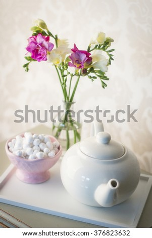 table decoration with teapot and freesias in vase  - stock photo