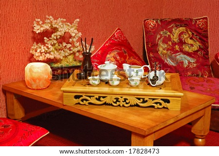 Table for tea ceremony in japanese or chinese restaurant. Interior in red tone. - stock photo