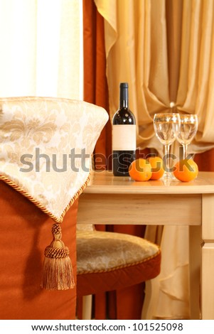 table fragment, on it a bottle of wine and two glasses, in the foreground a chair back