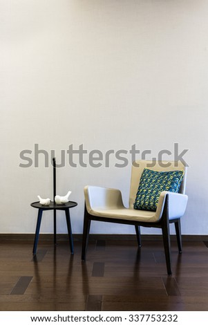Table Grey Armchair combination in front of a plain wall - stock photo