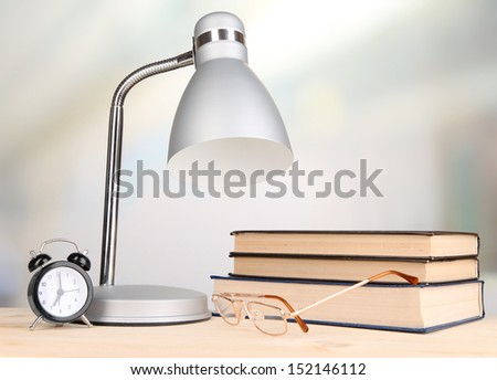 Table lamp and books on desk in room - stock photo