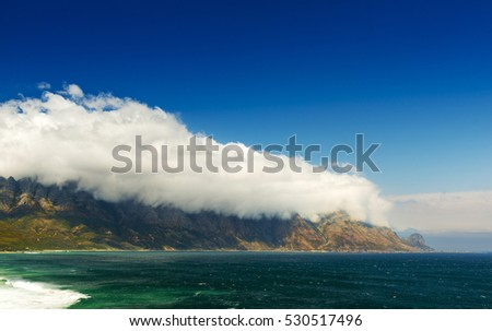 Table Mountain National Park coastline in South Africa with clouds over mountains