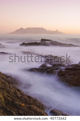Table mountain, South Africa from Blouberg beach at sunset. Taken with a slow shutter speed to enhance the waters movement. - stock photo