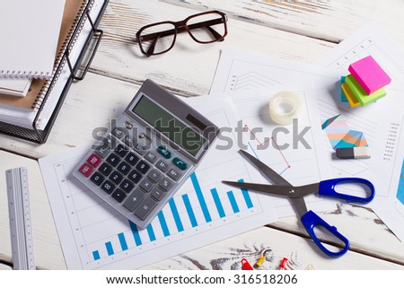 Table of accountant. Workplace of secretary. Stationery scattered on the table.