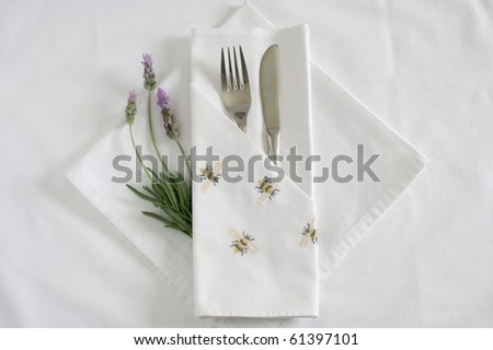 Table place setting with embroidered linen and lavender - stock photo