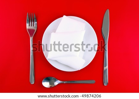 Table serving- knife, spoon, fork, spoon and silk napkin  a on red background.