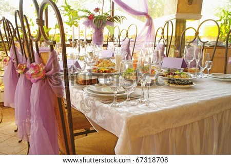 Table set for a wedding dinner decorated with flowers and a silk bow - stock photo
