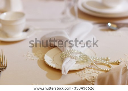 Table set for an event party or wedding reception decorated with pearls - stock photo